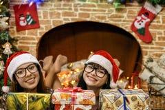 Deux filles près de la cheminée et de l'arbre de Noël Photos stock