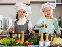 Deux filles préparant des légumes et souriant à l'intérieur Images stock