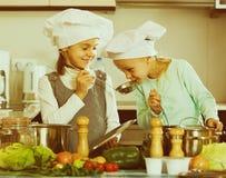 Deux filles préparant des légumes et souriant à l'intérieur Photographie stock
