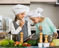 Deux filles préparant des légumes et souriant à l'intérieur Photo stock