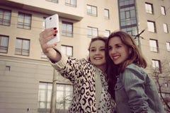 Deux filles prenant des photos d'elle-même et du sourire Image libre de droits