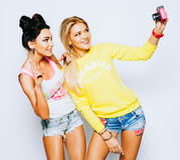 Deux filles prenant l'image d'individu ensemble sur l'appareil-photo rose de vinage, d'intérieur Photos libres de droits