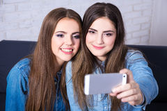 Deux filles prenant la photo de selfie avec le téléphone intelligent Photo stock