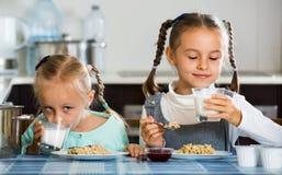 Deux filles prenant le petit déjeuner avec le gruau de farine d'avoine Photos stock