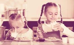 Deux filles prenant le petit déjeuner avec le gruau de farine d'avoine Image libre de droits
