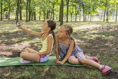 Deux filles prenant une photo en parc Les filles en parc font des selfies deux filles d'adolescent de beautifu font le selfie en  Image stock