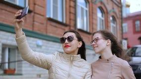 Deux filles prennent des selfies marchant autour de la ville clips vidéos