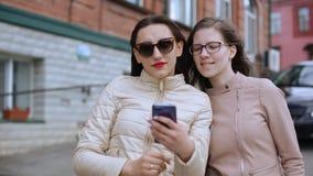 Deux filles prennent des selfies marchant autour de la ville banque de vidéos