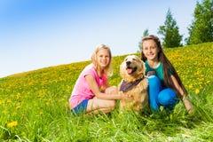 Deux filles presque s'asseyant au chien sur l'herbe verte Image libre de droits
