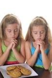 Deux filles priant au-dessus des biscuits Photographie stock