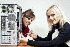 Deux filles réparant l'ordinateur Photos stock