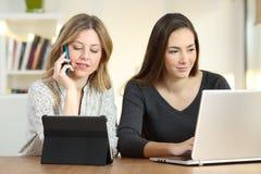 Deux filles recherchant le contenu utilisant les dispositifs multiples photographie stock