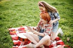 Deux filles regardant dans le comprimé le pique-nique Photo stock