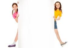 Deux filles regardant de la plaquette blanche, Image stock