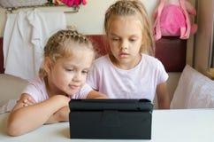 Deux filles regardant le comprimé dans le train Photographie stock libre de droits