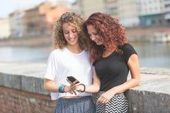 Deux filles regardant le téléphone intelligent dans la ville Images stock