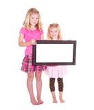 Deux filles retenant une trame blanc Photos stock