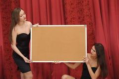 Deux filles retiennent le panneau vide Photo stock