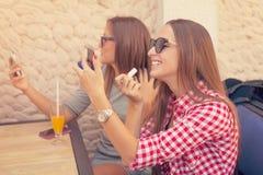 Deux filles riant et réparant le maquillage Photos stock