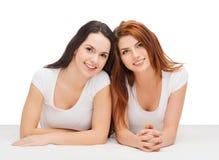 Deux filles riantes dans des T-shirts blancs Photos stock