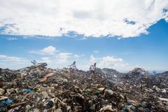 Deux filles s'élevant parmi des montagnes des déchets Photographie stock libre de droits