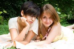 Deux filles s'étendant sur la couverture de lit sur l'herbe verte Photo libre de droits