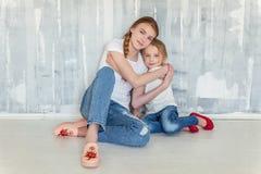 Deux filles s'asseyant au mur gris Images libres de droits