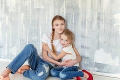 Deux filles s'asseyant au mur gris Photographie stock