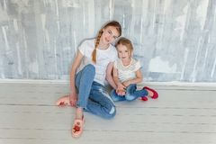 Deux filles s'asseyant au mur gris Image libre de droits