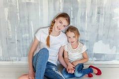 Deux filles s'asseyant au mur gris Photographie stock libre de droits