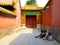 Deux filles s'asseyant au sol entre deux murs rouges Photographie stock