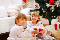 Deux filles s'asseyant avec des cadeaux s'approchent de l'arbre de Noël Images libres de droits