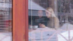 Deux filles s'asseyant en café et regardant le téléphone banque de vidéos