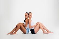 Deux filles s'asseyant sur l'étage Photos libres de droits