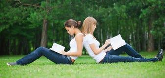 Deux filles s'asseyant sur l'herbe Photographie stock libre de droits