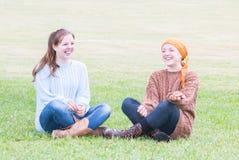 Deux filles s'asseyant sur l'herbe Photographie stock