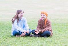 Deux filles s'asseyant sur l'herbe Photos stock