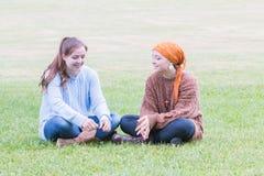 Deux filles s'asseyant sur l'herbe Image stock
