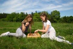 Deux filles s'asseyant sur l'herbe et jouant des échecs en parc Photos libres de droits