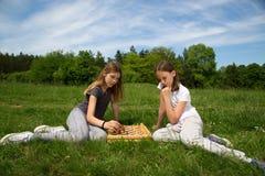 Deux filles s'asseyant sur l'herbe et jouant des échecs en parc Image libre de droits