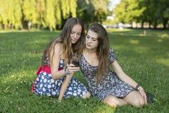 Deux filles s'asseyant sur l'herbe et utilisent un smartphone Photo libre de droits