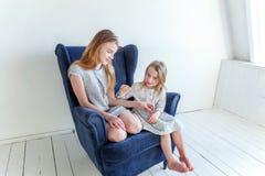 Deux filles s'asseyant sur la chaise bleue moderne Photo stock