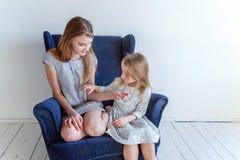 Deux filles s'asseyant sur la chaise bleue moderne photos libres de droits