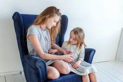 Deux filles s'asseyant sur la chaise bleue moderne Photographie stock libre de droits