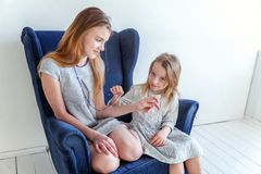 Deux filles s'asseyant sur la chaise bleue moderne Images libres de droits