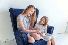 Deux filles s'asseyant sur la chaise bleue moderne Photos stock