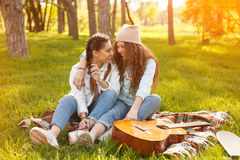 Deux filles s'asseyant sur la couverture en parc Photographie stock