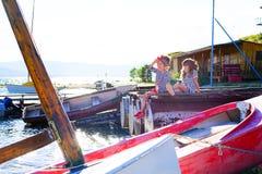 Deux filles s'asseyant sur le dock Image stock