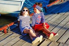 Deux filles s'asseyant sur le dock Photos libres de droits