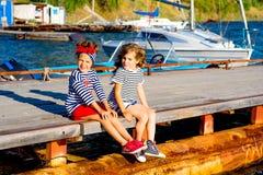 Deux filles s'asseyant sur le dock Photographie stock